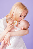 Mom feeds the baby bottle. In studio Stock Images