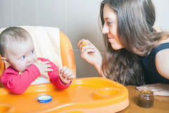 Mom feeds the baby puree. Healthy and natural baby food. Stock Image