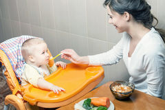 Mom feeds the baby soup. Healthy and natural baby food Stock Images