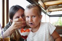 Mom feeds daughter ice cream Royalty Free Stock Photo