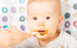 Mom feeds funny baby from  spoon Stock Images