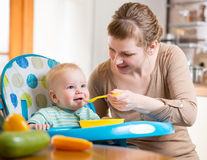Mom feeds funny baby with spoon Royalty Free Stock Photography