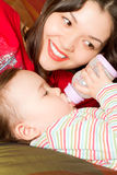 Mom feeds her baby with a bottle Royalty Free Stock Images