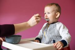 Mom feeds her beautiful baby with a spoon. Healthy Chicken Soup stock images