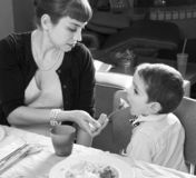 Mom feeds her son on Thanksgiving turkey stock image