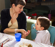 Mom feeds her son on Thanksgiving turkey Royalty Free Stock Images