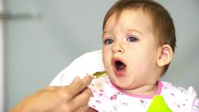 Mom feeds a small child with a spoonful of vegetables. Child does not like vegetables.
