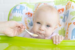 Free Mom Feeds The Baby With A Spoon Royalty Free Stock Photo - 128442995