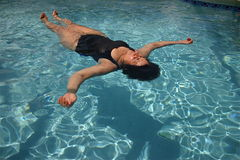 Mom Floats in Summer. Middle-aged woman floating on back in pool Stock Image