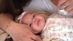 Ένα οικογενειακό χαμόγελο στο κρεβάτι, όπου mom κοιτάζει, αγγίζει και μιλά με την λίγη κόρη φιλμ μικρού μήκους