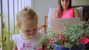 Mom freelancer works at the computer, talking on Skype, the daughter is bored and studies the potted plant, slow motion. stock video footage
