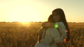 Mom gently hugs daughter against backdrop of a beautiful sunset. happy family concept. adult daughter in arms of her stock footage