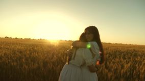 Mom gently hugs daughter against backdrop of a beautiful sunset. happy family concept. adult daughter in arms of her stock video footage