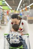 Mom gently kisses his young son in the supermarket.  stock images