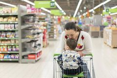 Mom gently kisses his young son in the supermarket.  Stock Photos