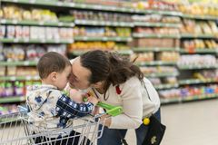 Mom gently kisses his young son in the supermarket.  Royalty Free Stock Image