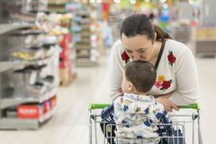 Mom gently kisses his young son in the supermarket.  Royalty Free Stock Images