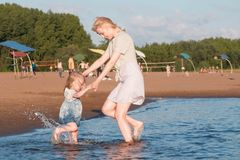 Mom and girl playing on the beach of the river at sunset and swim. stock images