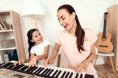 Mom and girl are playing the synthesizer at home. They rest and have fun. Behind them are bookshelves and a white wall stock photos