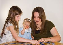 Mom and Girls Doing Puzzle Royalty Free Stock Images
