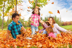Mom and girls throw leaves up in the air. Playing with kids in autumn park happy and smiling Royalty Free Stock Photography