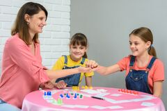 Mom gives cubes to daughter playing board games