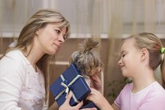 Mom gives the daughter a dog for her birthday.  royalty free stock image