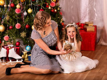 Mom gives daughter doll near Christmas tree. Stock Photos