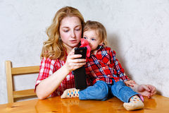 Mom gives daughter drink from a bottle Stock Images