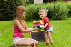 Mom gives daughter a lot of books. Royalty Free Stock Images