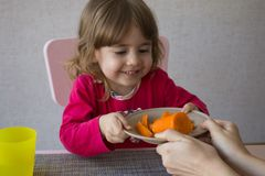 Mom gives daughter a plate of carrots Royalty Free Stock Images