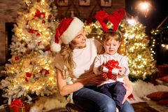 Mom gives a gift in a box to her son in a room on Christmas Day. Mom gives a gift in a box to her son in a room with a Christmas tree and a fireplace on royalty free stock images