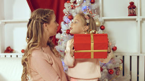 Mom gives a gift to the daughter near the Christmas tree Stock Photos