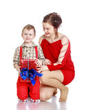 Mom gives a gift to his son. Joyful grey-eyed,fair-haired boy in a long red shorts with straps and a plaid shirt.And his mother , a beautiful young women in a stock image