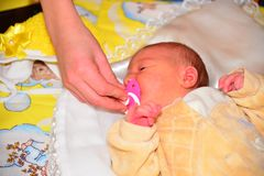 Mom gives newborn baby a pacifier royalty free stock photos