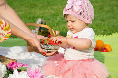 Mom gives a strawberry child Royalty Free Stock Photography