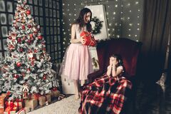 Mom gives a surprise gift to her daughter before the New Year tree. The daughter covered her eyes with her hands