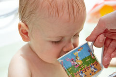 Mom gives to drink from a cup baby Royalty Free Stock Photo