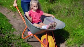 Mom Giving Child Daughter Ride In Wheelbarrow stock footage
