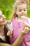 Mom giving dandelion to daughter Royalty Free Stock Photography