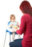 Mom giving food to her son on high chair Royalty Free Stock Photo