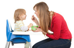 Mom giving food to her son on high chair Stock Photos