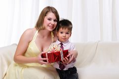 Mom giving a gift to his son. Sitting on a white sofa Royalty Free Stock Image