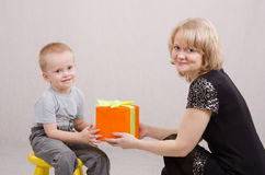 Mom giving a gift to his son. Five year old mother congratulates and gives gifts royalty free stock image