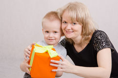 Mom giving a gift to his son. Five year old mother congratulates and gives gifts royalty free stock photos
