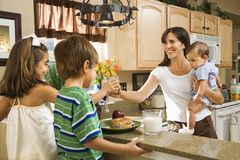 Mom giving kids breakfast. Hispanic family in kitchen with breakfast royalty free stock photography