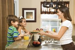Mom giving kids breakfast. Royalty Free Stock Photo