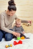 Mom Giving Plastic Toys to her Crying Baby Royalty Free Stock Photos