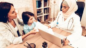 Mom Giving to Arabic Doctor Medical Examinations. Confident Muslim Female Doctor. Child at the Pediatrician. Hospital Concept. Healthy Concept. Child Patient stock photography