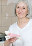 Mom/Grandma In The Kitchen. Senior woman standing in front of the stove smiling stock photography